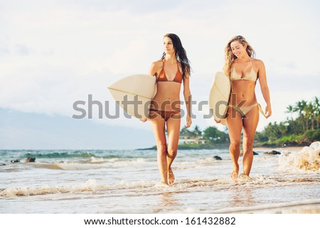 Beautiful Sexy Surfer Girls on the Beach at Sunset - stock photo