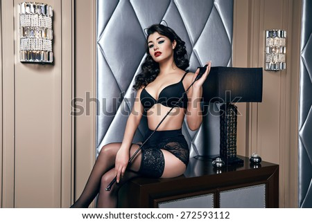 Beautiful sexy tanned brunette woman with  in black lace lingerie with a beautiful evening makeup sitting on the table next to wall hand strap with shoulder red lips perfect body