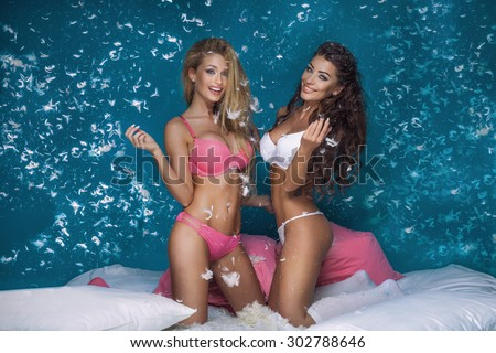 Beautiful sexy two girls having fun in bedroom, pillow fight. Blonde woman and brunette lady smiling, looking at camera.  - stock photo