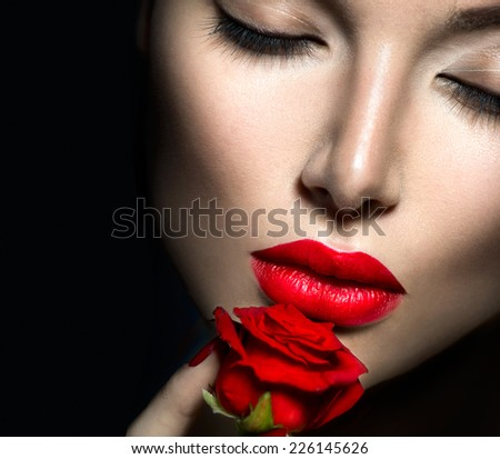 Beautiful Sexy Woman face closeup, makeup with Red Lips, Nails and Rose Flower. Beauty Girl. Passion. Makeup and Manicure. Sensual Mouth. Sexy Red Color Lips. Isolated on black background