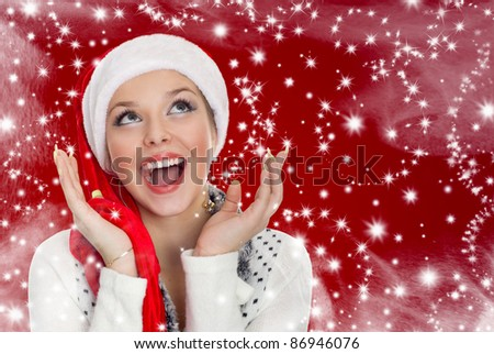 beautiful sexy woman in a santa hat on red background - stock photo