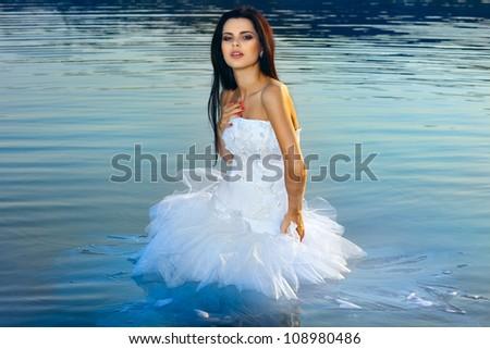 Beautiful sexy woman in a wedding-dress in water - stock photo
