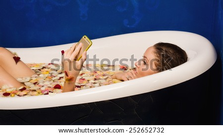 Beautiful sexy woman in bath with flowers petals while using the smart phone. she is doing a selfie - stock photo