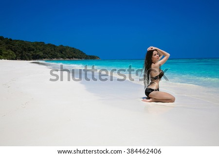 Beautiful sexy woman in black bikini relaxing on exotic tropical beach beside blue water by seashore. Summer vacation. Sun tanning girl on white sand. - stock photo