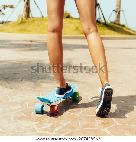 Beautiful sexy woman in blue and white striped bikini rides her penny board longboard with multi colored wheels at the park