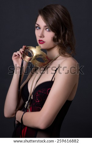 beautiful sexy woman in lingerie posing with mask over grey background - stock photo