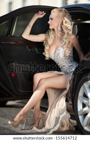 Beautiful Sexy woman in luxury car with long legs. Rich lifestyle. gorgeous blonde girl with car. Vogue style model. Happy woman smiling at luxury auto. Portrait of attractive rich woman. Woman driver - stock photo