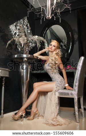 beautiful sexy woman in luxury interior glamour fashion. gorgeous blonde girl in hotel. vogue style fashion woman in trendy evening dress. Beauty and jewelry model. Rich woman at retro villa. Vintage  - stock photo