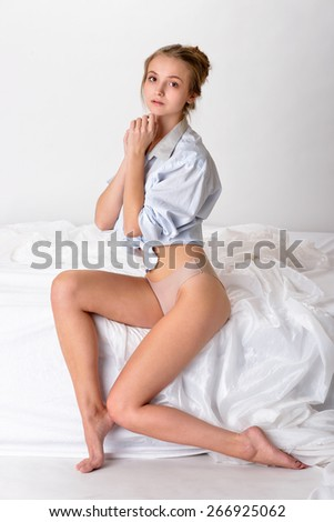 Beautiful sexy woman in shirt and panties sitting on white bed. Studio shooting with white background. - stock photo