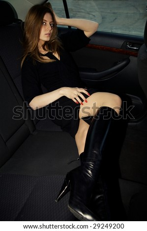 Beautiful sexy woman in the back seat of a car - stock photo