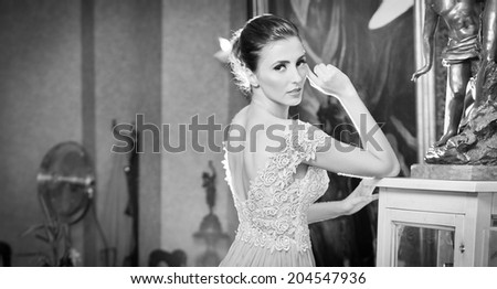 Beautiful sexy woman in white lace dress in vintage scenery. Portrait of brunette young women with creative hair cut posing in luxury indoor. Attractive young fashionable female, black and white photo - stock photo