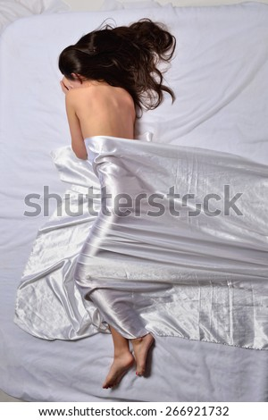 Beautiful sexy woman  laying on white bed under draped linen. View from above.