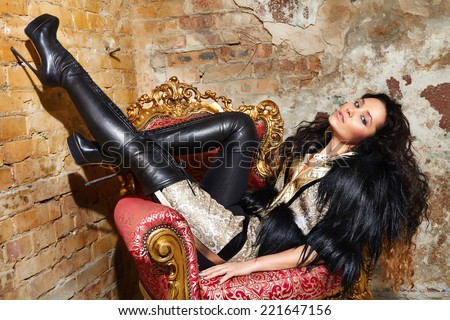 Beautiful sexy woman long brunette hair in black fur Treads on high heel gold pans sitting on the chair red brick wall background makeup fashion style - stock photo