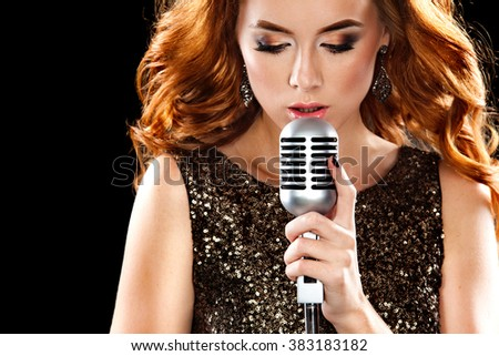 Beautiful sexy woman singing with the microphone