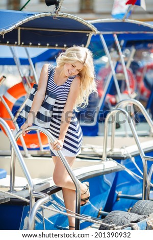 Beautiful sexy woman wearing sailor striped dress posing at the sea. Adorable woman wearing sea Captain's cap and sexy sailor T-shirt - stock photo