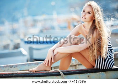 Beautiful sexy woman wearing sailor striped dress posing in boat - stock photo