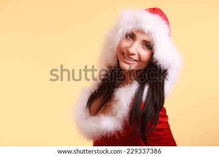 Beautiful sexy woman wearing santa claus costume clothes on yellow background