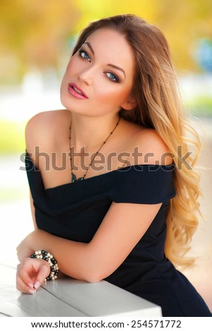 Beautiful sexy woman with black dress and blond hair posing outdoor. Fashion girl - stock photo