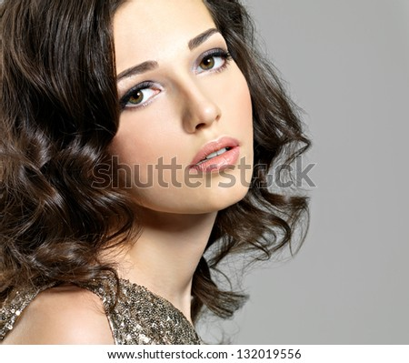 Beautiful sexy woman with broun curly hairs poses at studio - stock photo