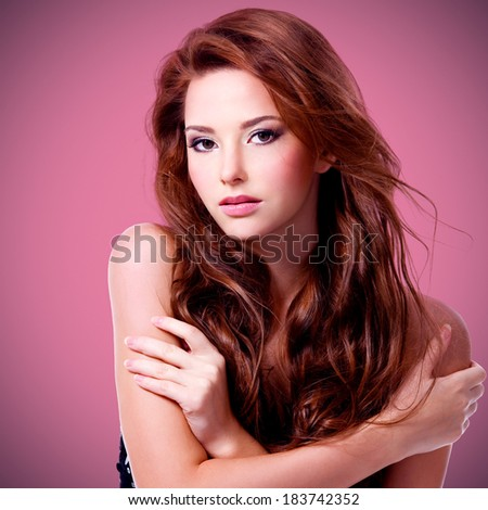 Beautiful sexy woman with brown long hairs posing at studio - stock photo