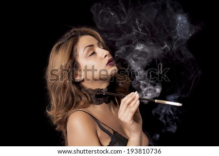 Beautiful sexy woman with cigarette holder smoking