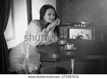 Beautiful sexy woman with coffee in the kitchen