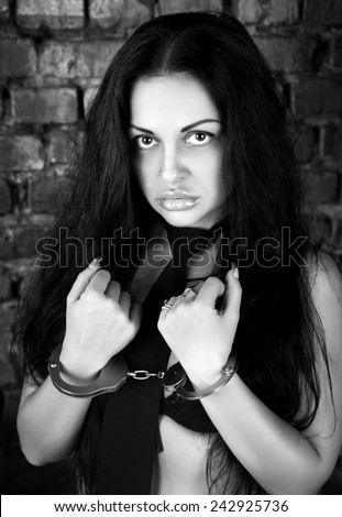 Beautiful sexy woman with long black straight hair, beautiful face, big lips, perfect body, white & black photo. Sexy girl in black tie of police woman role playing games. - stock photo