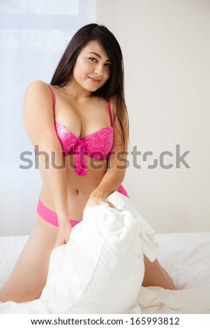 Beautiful Sexy Woman with long hair about to engage in a pillow fight - stock photo