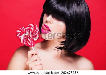 Beautiful sexy woman with pink lips with lollipop on red - stock photo