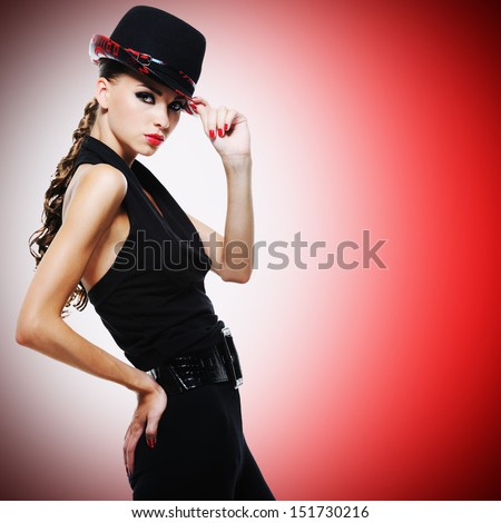 Beautiful sexy woman with red lips and nails in modern black hat