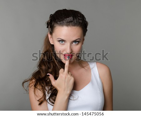 Beautiful sexy woman with red lips and showing middle finger obscene gesture - stock photo