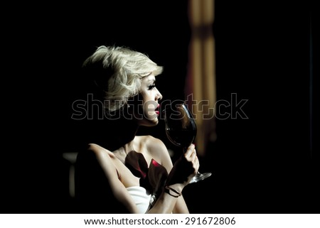 Beautiful sexy young blond lady with bright makeup drinking red wine from goblet looking away, horizontal picture - stock photo