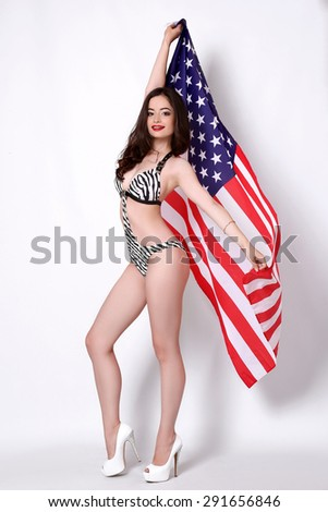 Beautiful, sexy, young brunette woman in style swimsuit posing with national usa flag in background. 4th july concept. - stock photo