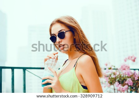 Beautiful sexy young brunette woman with long wavy hair thin slender figure perfect body and pretty face make-up wearing,jewelry.summer accessory,smoothies on a background of a swimming pool, hotel - stock photo
