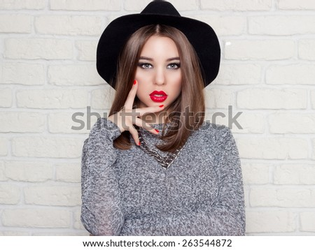 beautiful sexy young girl in a black hat with red full lips, bright makeup and painted my nails red - stock photo