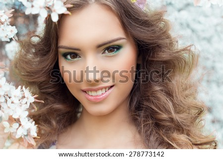 beautiful sexy young tender sweet smiling girl in a flowered garden with beautiful makeup - stock photo