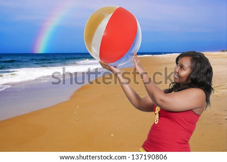 Beautiful sexy young woman at the beach with a rainbow - stock photo