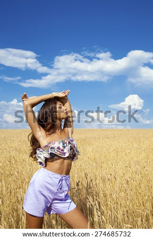Beautiful sexy young woman in blue shorts in a wheat golden field - stock photo