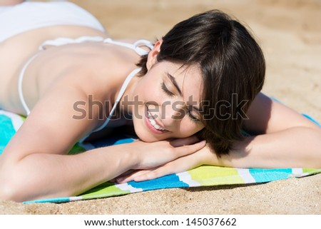 Beautiful sexy young woman relaxing sunbathing on the beach lying on a towel with her eyes closed and a blissful smile - stock photo