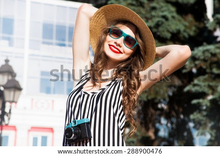 Beautiful sexy young woman with brunette hair matched up with an evening make-up natural red lipstick in stylish glasses for vision wearing a black T-shirt and jeans clothed thigh ideal body,smiling  - stock photo