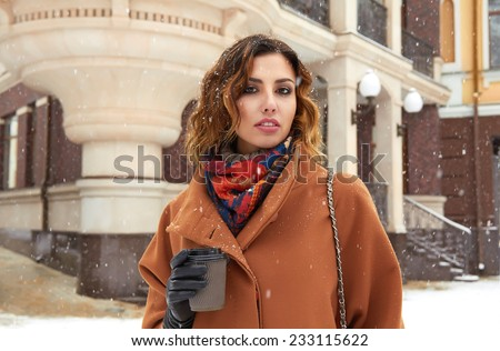 Beautiful sexy young woman with curly brown hair with bright makeup wearing a brown coat goes on snow-covered street past the shops with a cup of hot coffee, cappuccino, tea, Christmas New Year Winter - stock photo