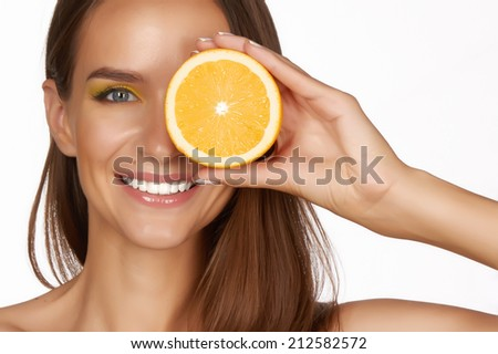 Beautiful sexy young woman with perfect healthy skin and long brown hair day makeup bare shoulders holding orange lemon grapefruit healthy eating organic food diet weight loss - stock photo