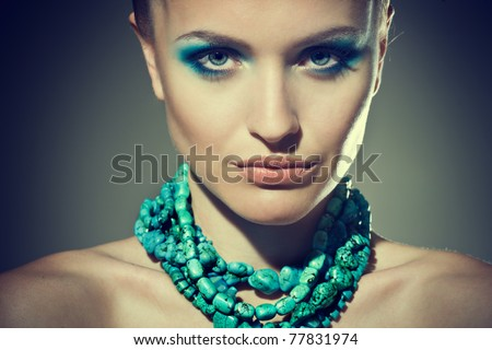 Beautiful sexy young woman with turquoise makeup and accessories - stock photo