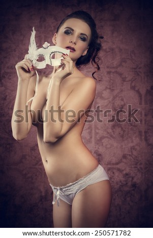 Beautiful, sexym nude brunette woman in white lingerie and carnival white mask. She has got nice dark make up. - stock photo