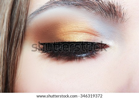 Beautiful shape of female eye with golden-brown cosmetic make-up