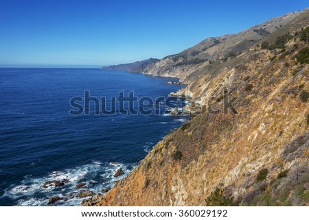 Beautiful shimmering  blue sea, ocean,  and white puffy clouds, along steep sheer jagged cliffs, near Carmel, CA. traveling the Big Sur Highway (Highway 1), on the California Central Coast - stock photo