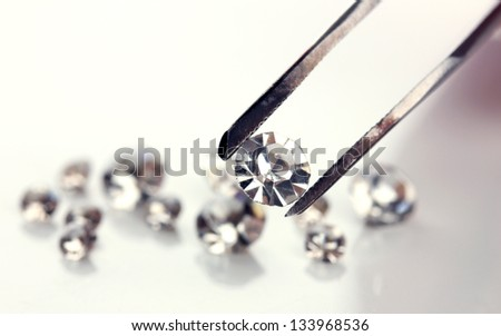 Beautiful shining crystal (diamond) in the tweezers, isolated on white - stock photo