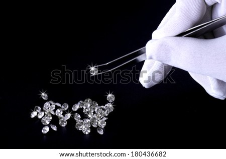 Beautiful shining crystal (diamond) in the tweezers, on black background - stock photo