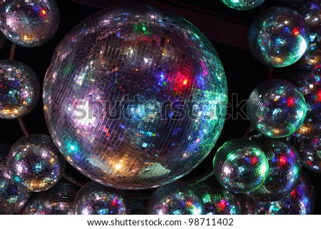 Beautiful shiny balls with colorful lights on ceiling in night club - stock photo