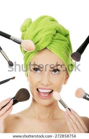 Beautiful shocked woman has brushes around face. - stock photo